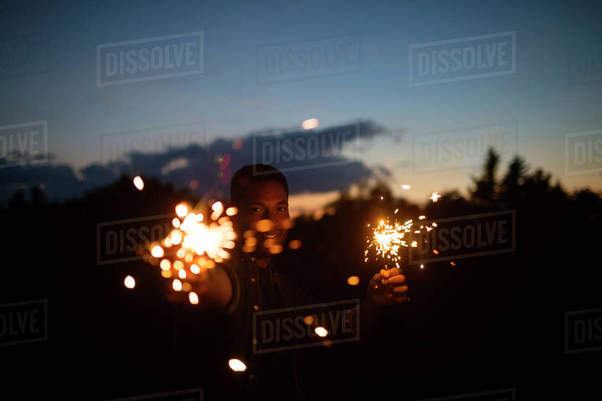 Portrait of man holding sparklers against sky at night Royalty-free stock photo