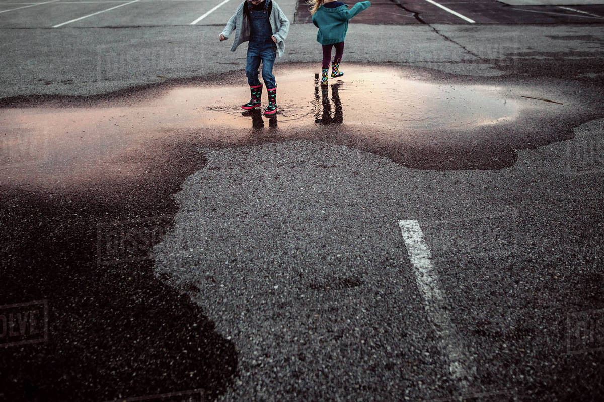Low section of sisters playing in puddle Royalty-free stock photo