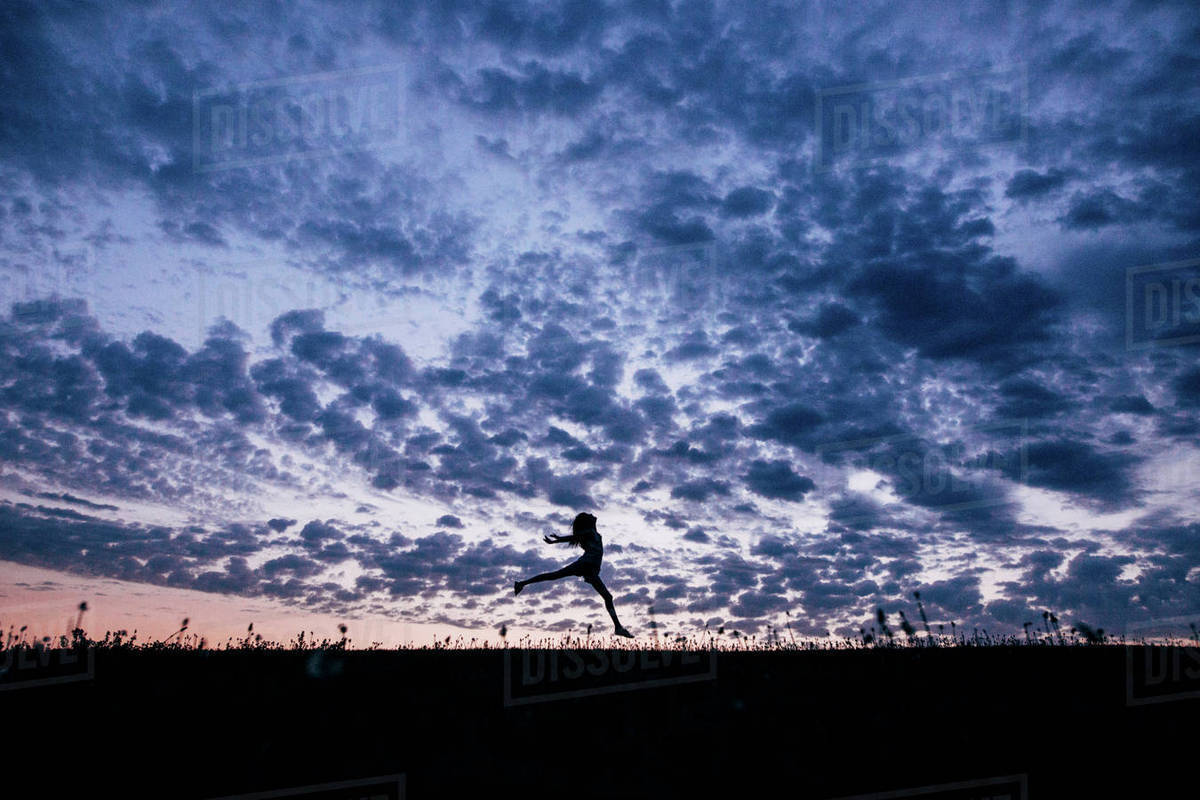 Silhouette girl jumping on field against dramatic sky Royalty-free stock photo