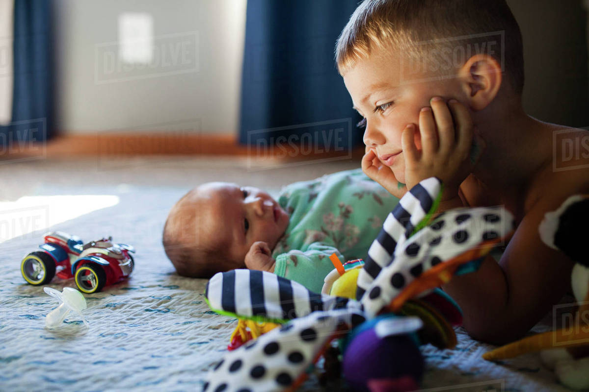 Boy looking at baby girl while lying on bed Royalty-free stock photo