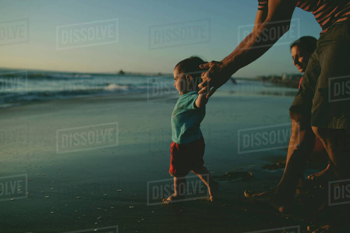 Father helping son to walk on sea shore against clear sky at dusk Royalty-free stock photo