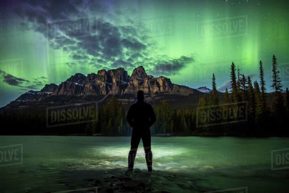 Man Standing Under Aurora Borealis In Banff National Park, Canada Royalty-free stock photo