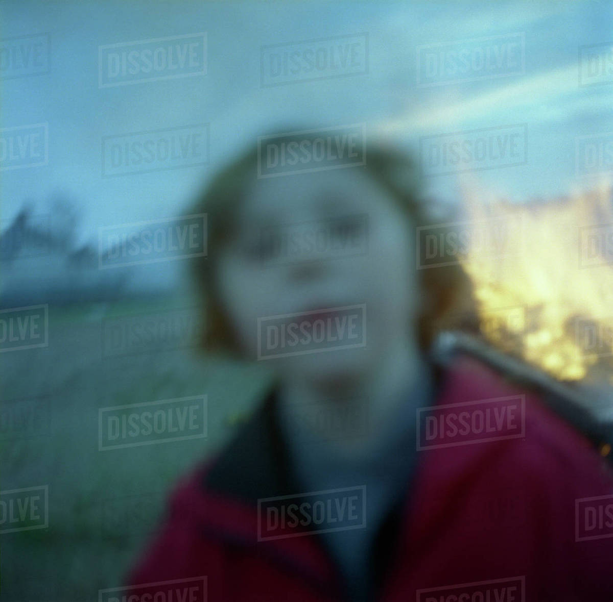 Blurred image of a young girl looking at the camera while playing around a bonfire in Mayhill, Swansea, South Wales Rights-managed stock photo