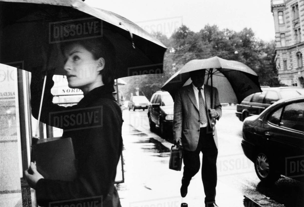 Woman standing in front of kiosk and man walking down the street both holding umbrellas Rights-managed stock photo