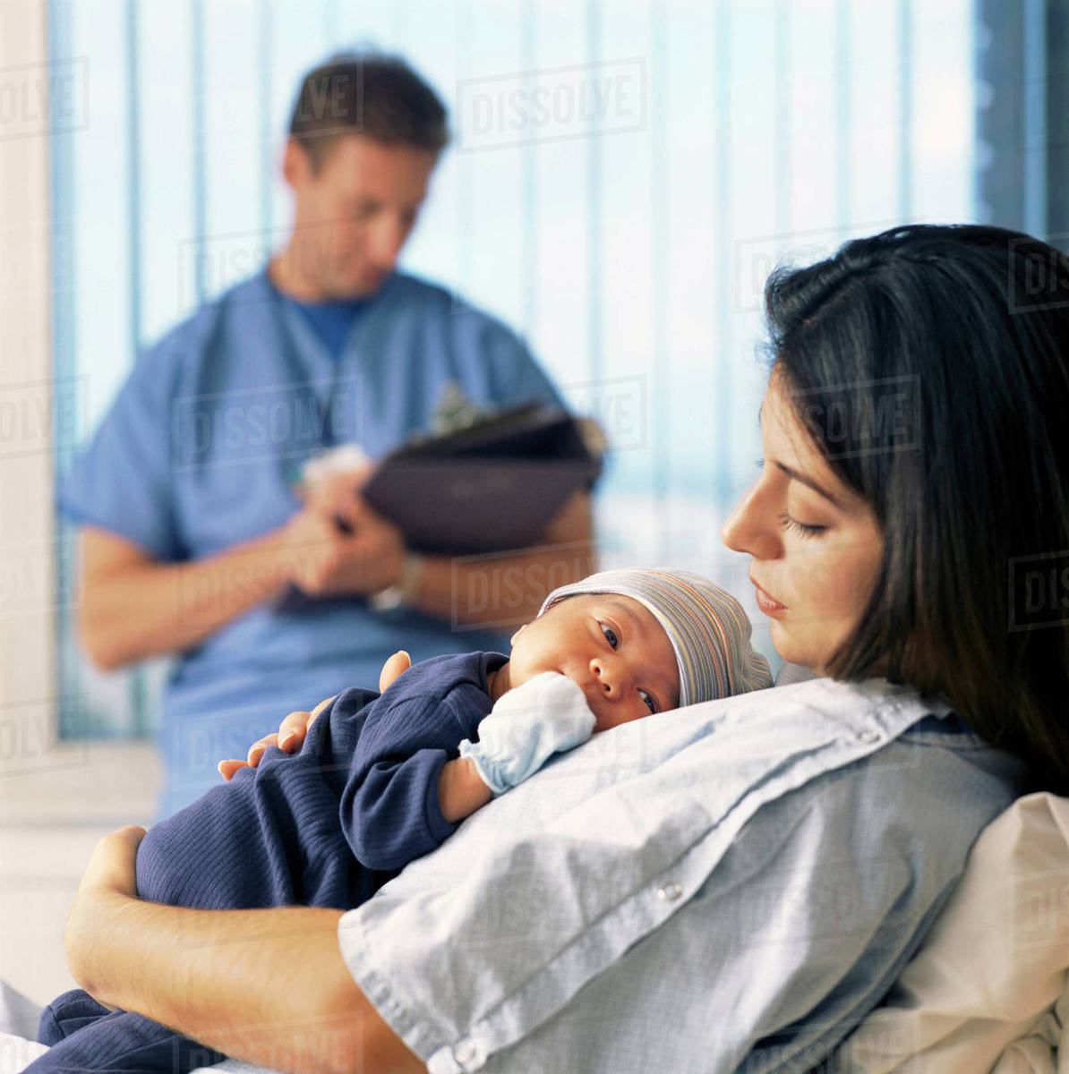 Mother holding baby in hospital bed with doctor in background Royalty-free stock photo