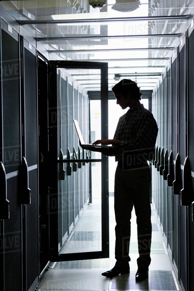 Technician with laptop, checking aisle of server storage cabinets in data center Royalty-free stock photo