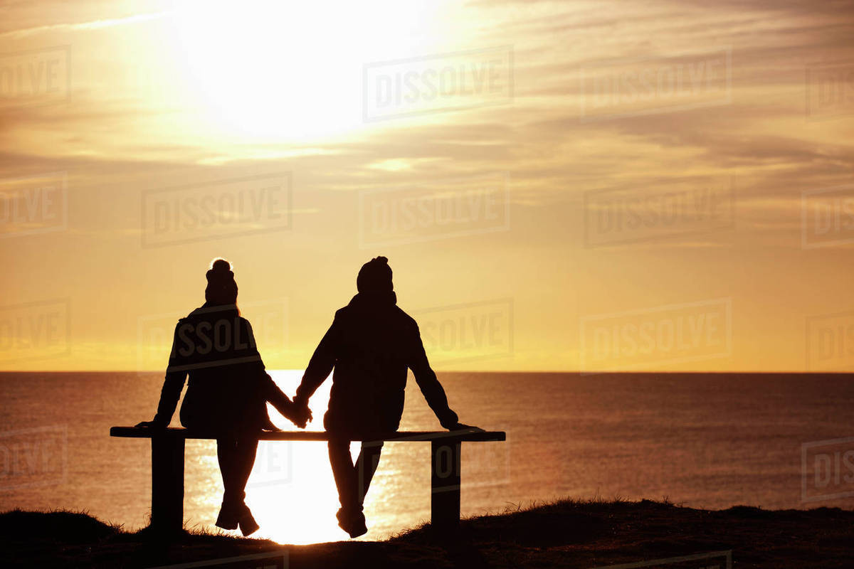 silhouette of couple sitting on bench holding hands against sunset over the ocean