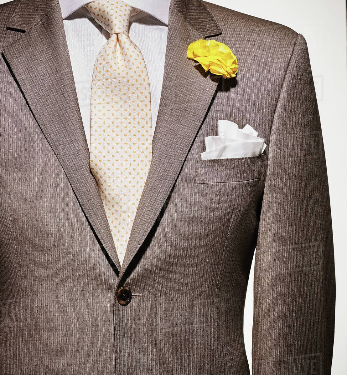 Detail of a light brown suit jacket with cream colored shirt and ...