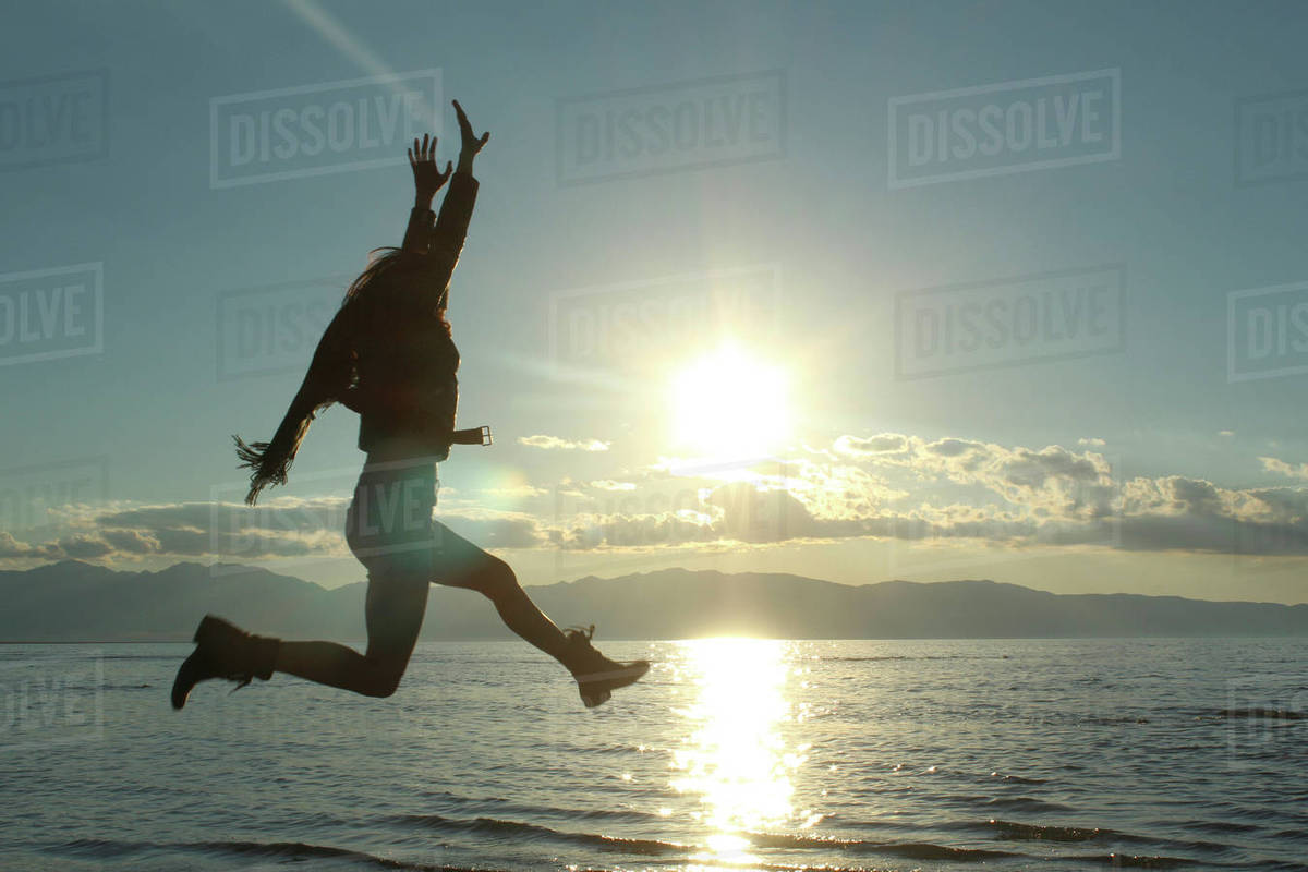 Cheerful woman jumping by lake against sky Royalty-free stock photo
