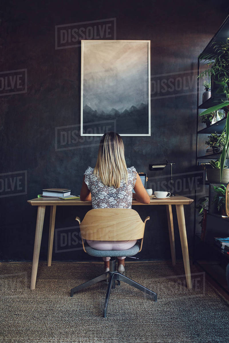 Rear view of businesswoman working while sitting at table in home office Royalty-free stock photo
