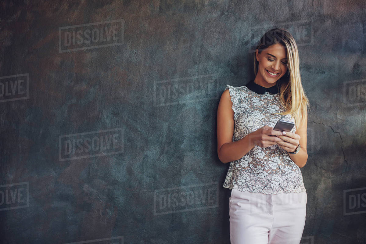 Happy businesswoman using smart phone while standing against wall at home office Royalty-free stock photo