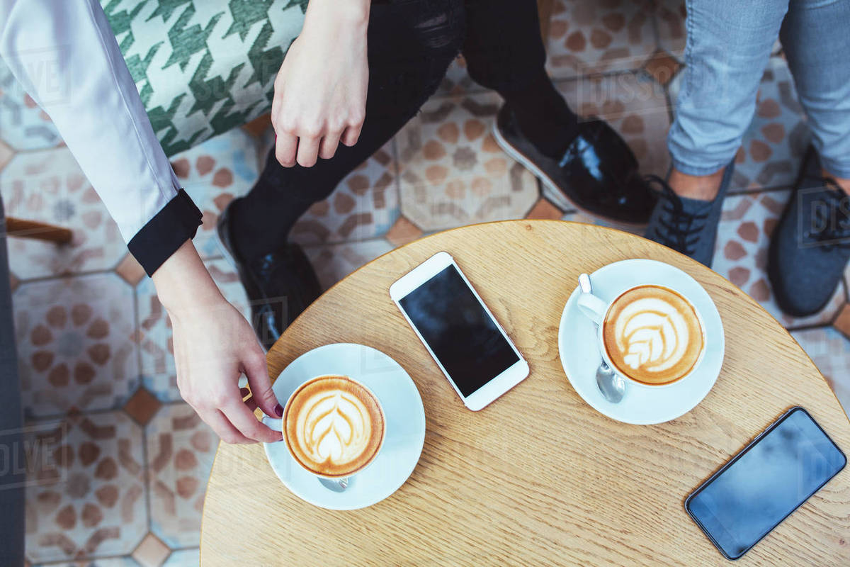 Low section of businesswomen with coffee and mobile phones on table in cafe Royalty-free stock photo