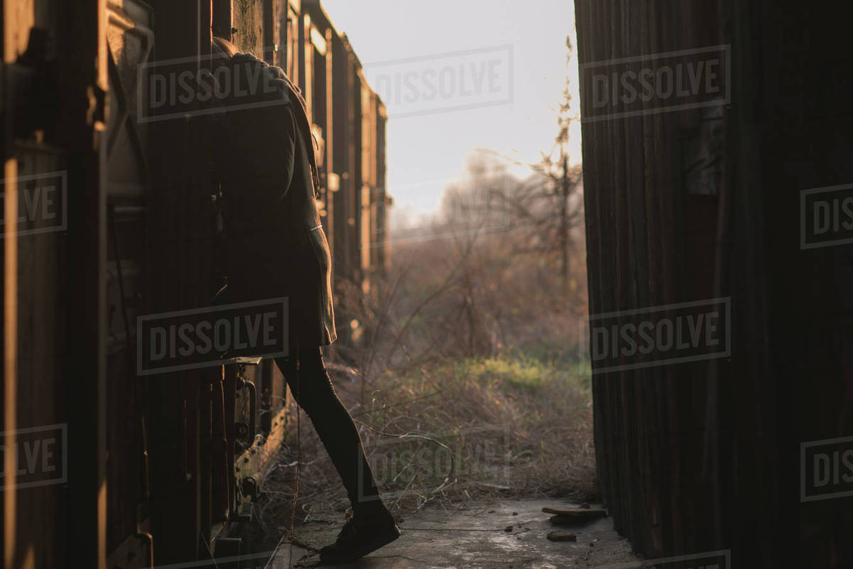 Side view of woman walking in abandoned train at sunset Royalty-free stock photo