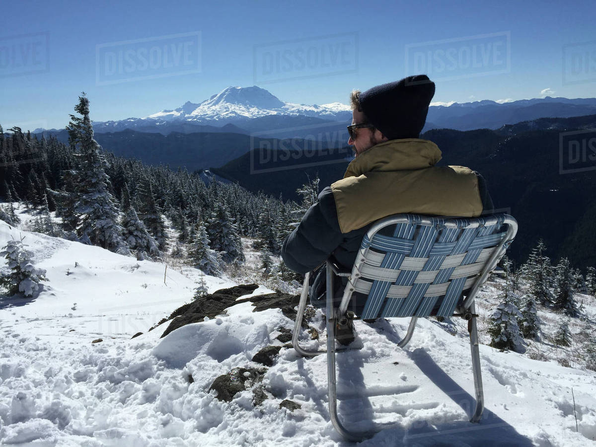 Rear view of man sitting on deck chair in snow covered field Royalty-free stock photo