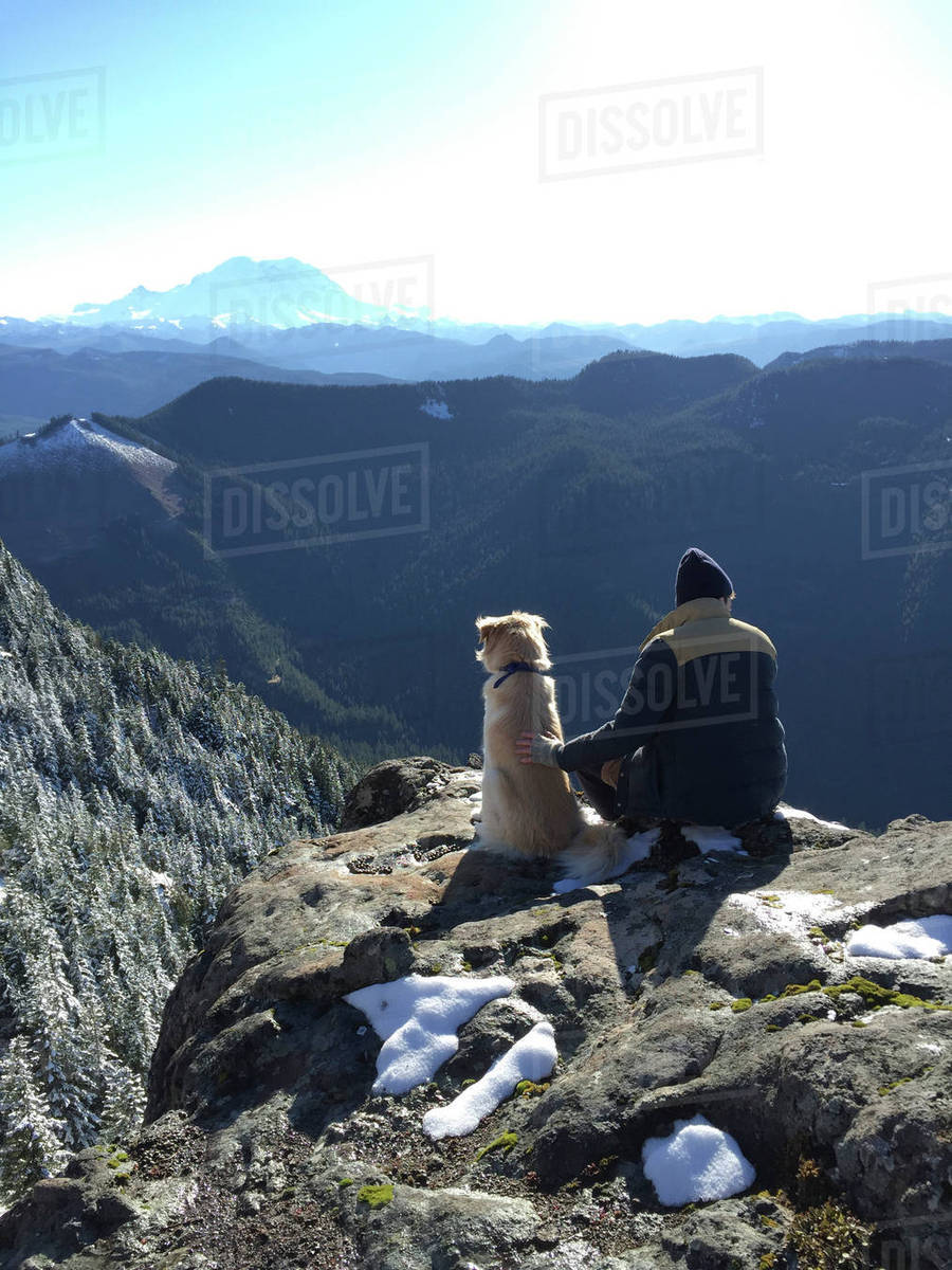 Rear view of man with dog sitting on rock against mountain Royalty-free stock photo