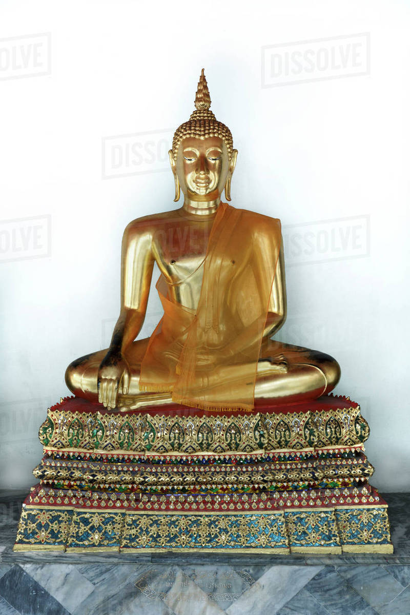 Golden Buddha statue against white wall Royalty-free stock photo