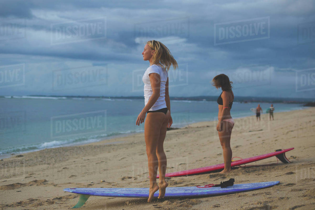 Female friends standing with surfboards at beach against cloudy sky Royalty-free stock photo