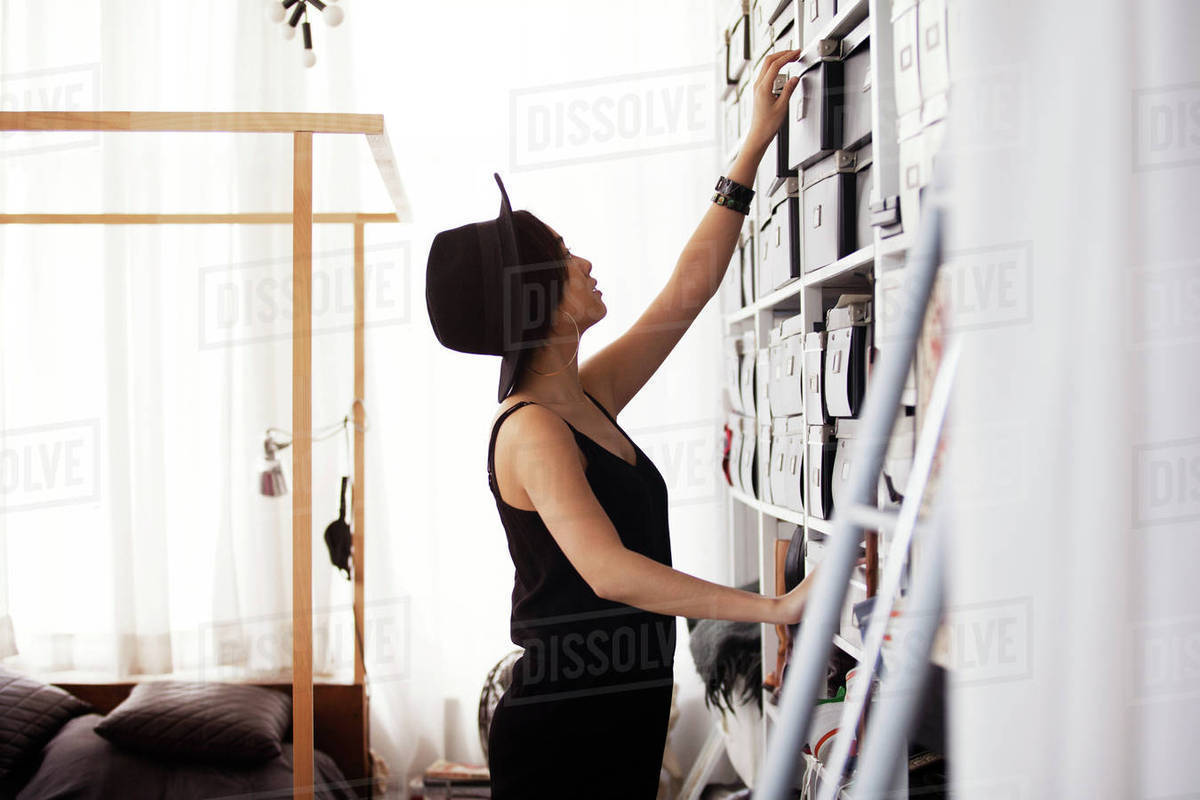 Side view of woman removing box from shelves in bedroom Royalty-free stock photo