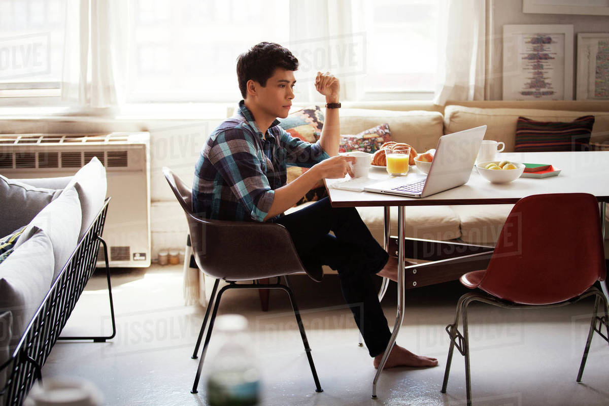 Side view of man using laptop while having breakfast at home Royalty-free stock photo