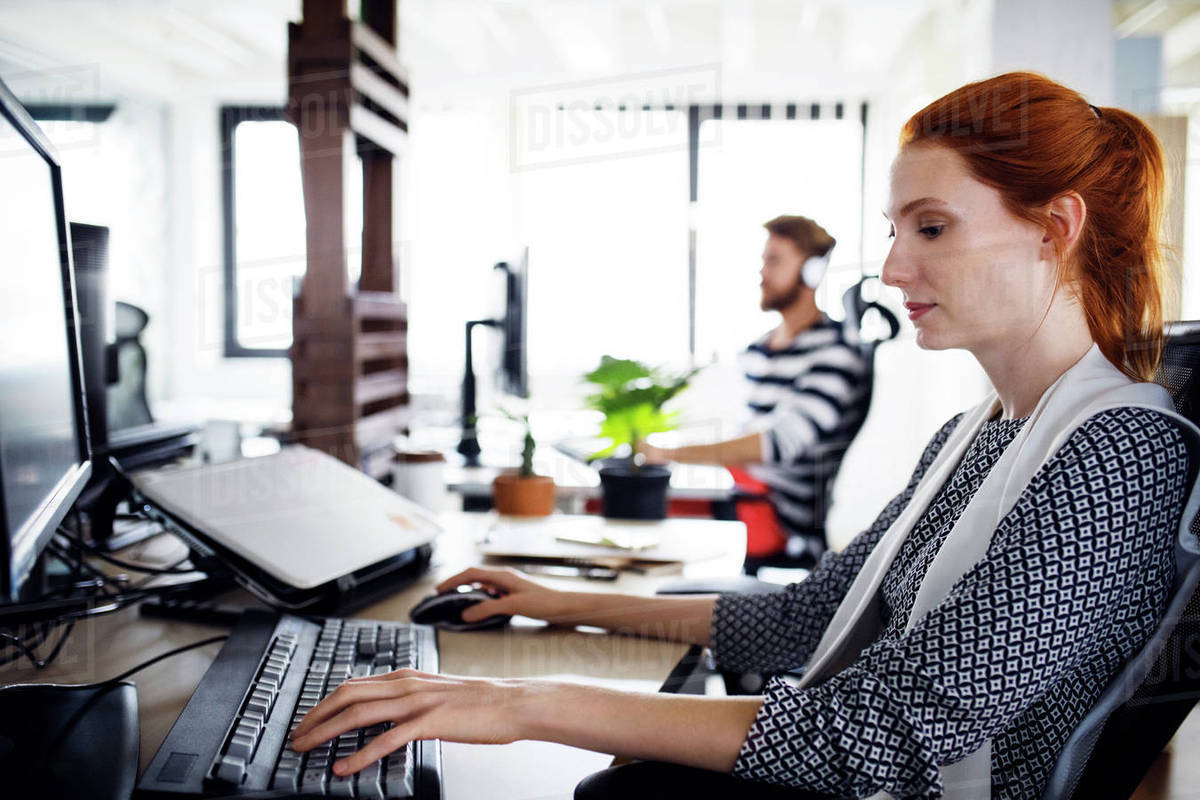 Side view of businesswoman using computer in creative office Royalty-free stock photo