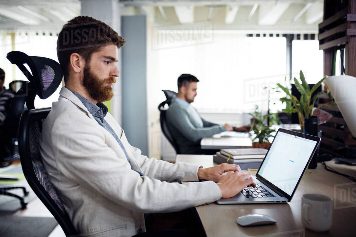 Side view of businessman using laptop in creative office Royalty-free stock photo