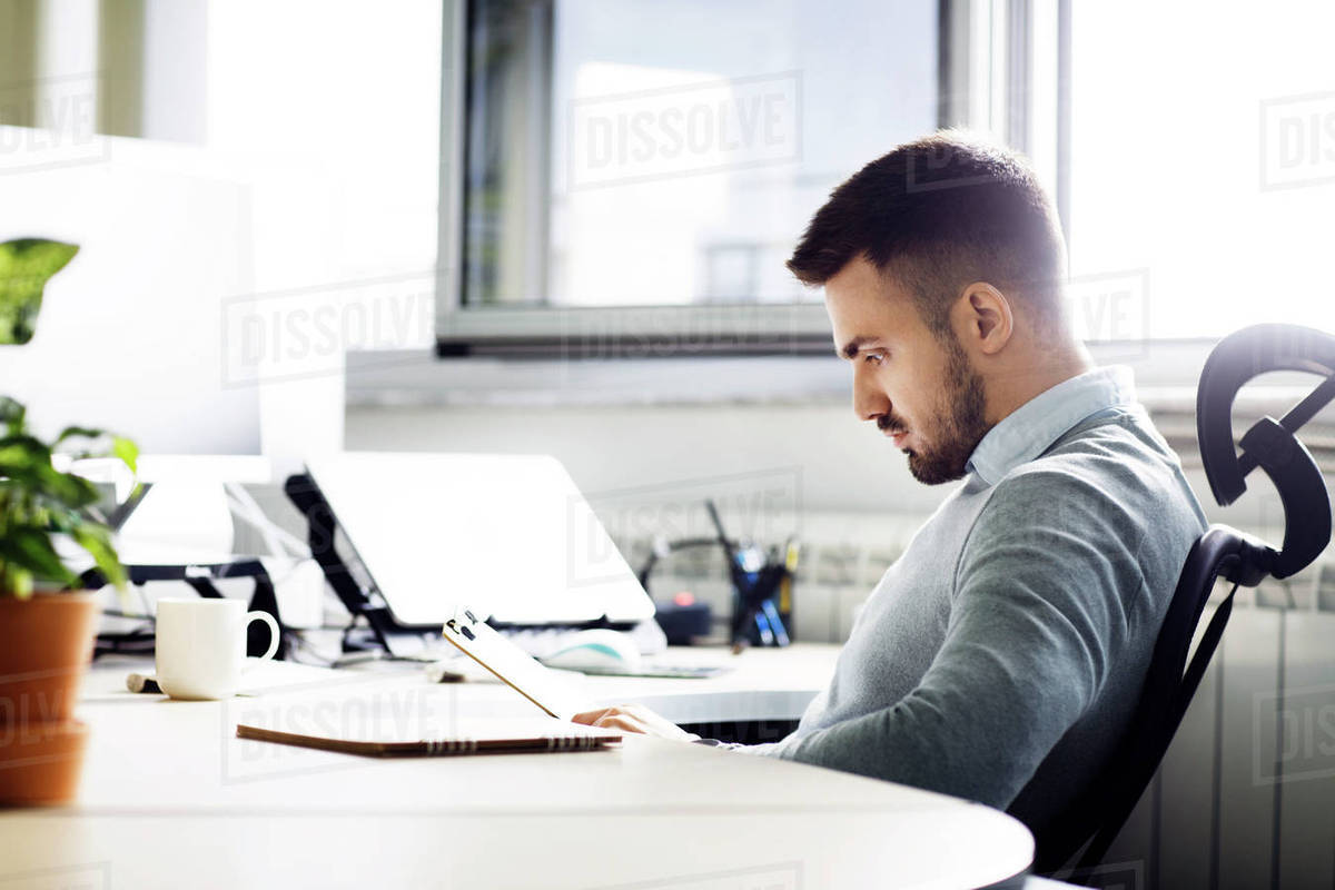 Side view of businessman reading document on clipboard in creative office Royalty-free stock photo