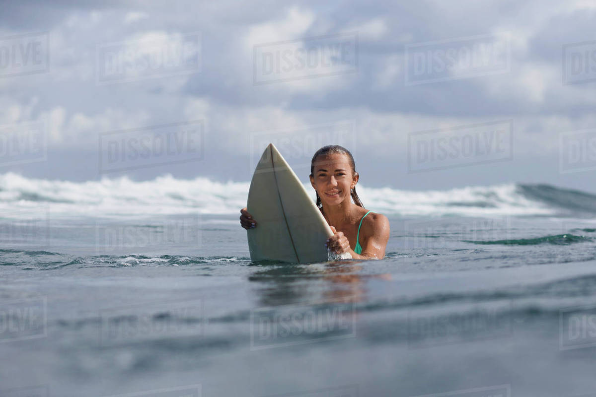 Portrait of woman holding surfboard in sea against sky Royalty-free stock photo