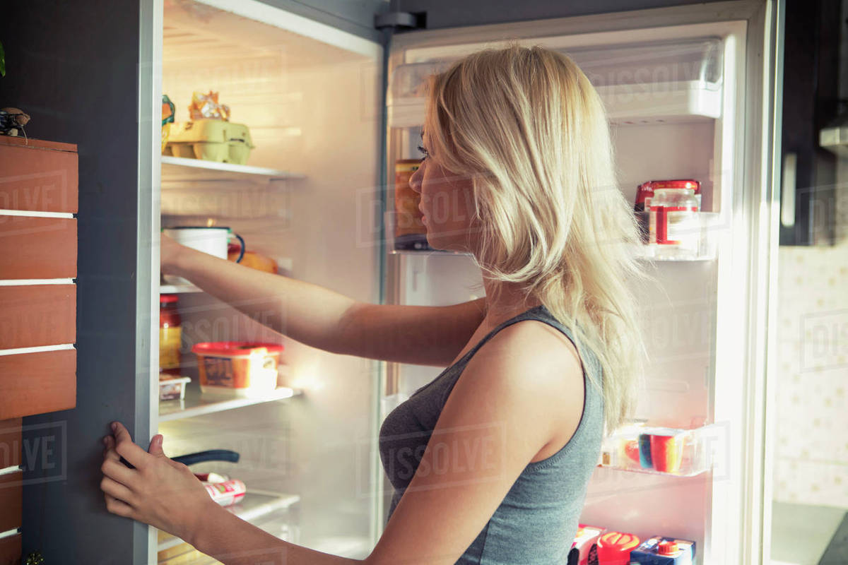 Side view of teenage girl looking in refrigerator at kitchen Royalty-free stock photo