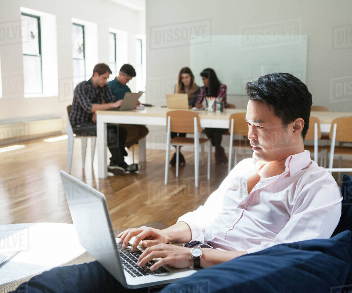 Businessman using laptop while sitting on sofa with colleagues working in background