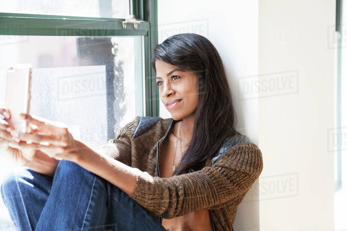 Smiling businesswoman taking selfie through smart phone while sitting on window sill in creative office