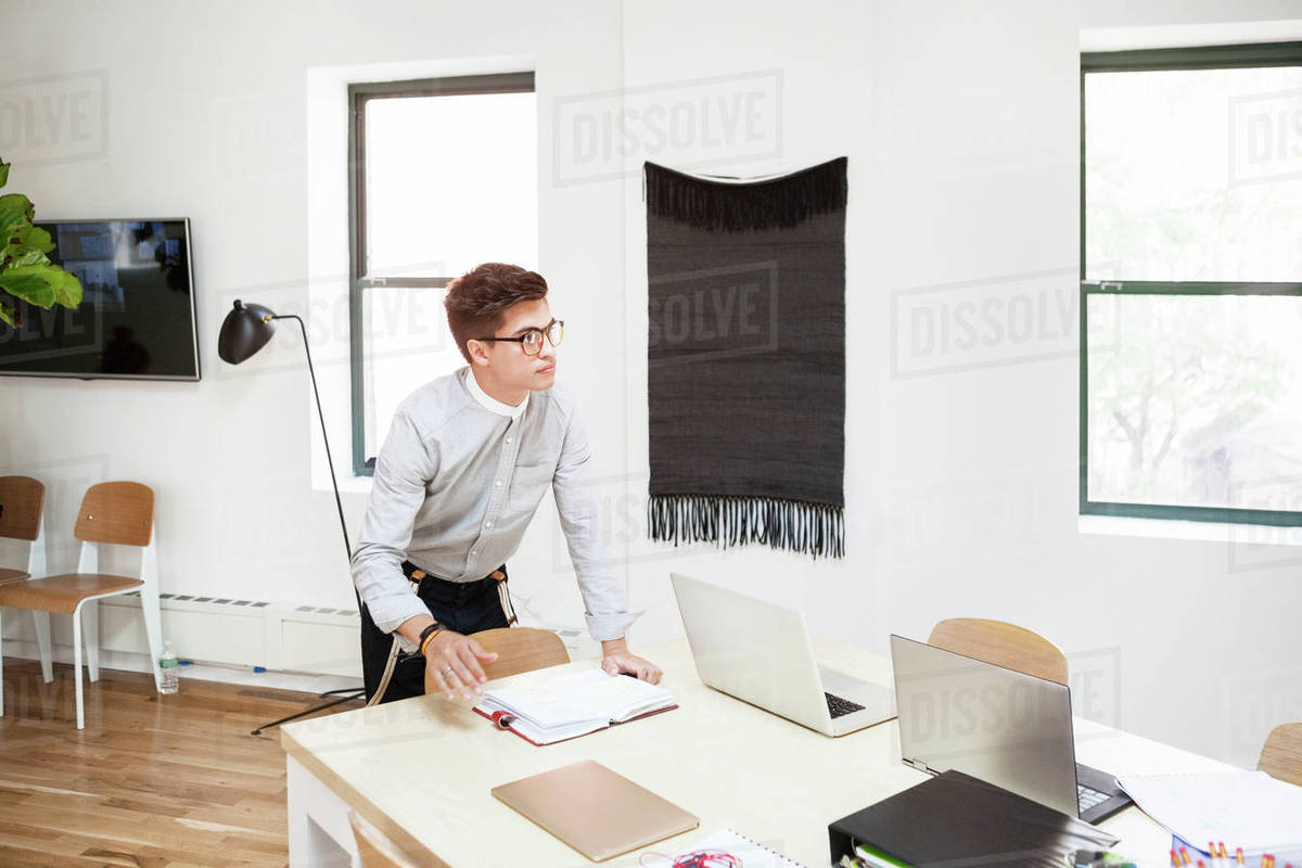 Thoughtful businessman standing at desk in creative office