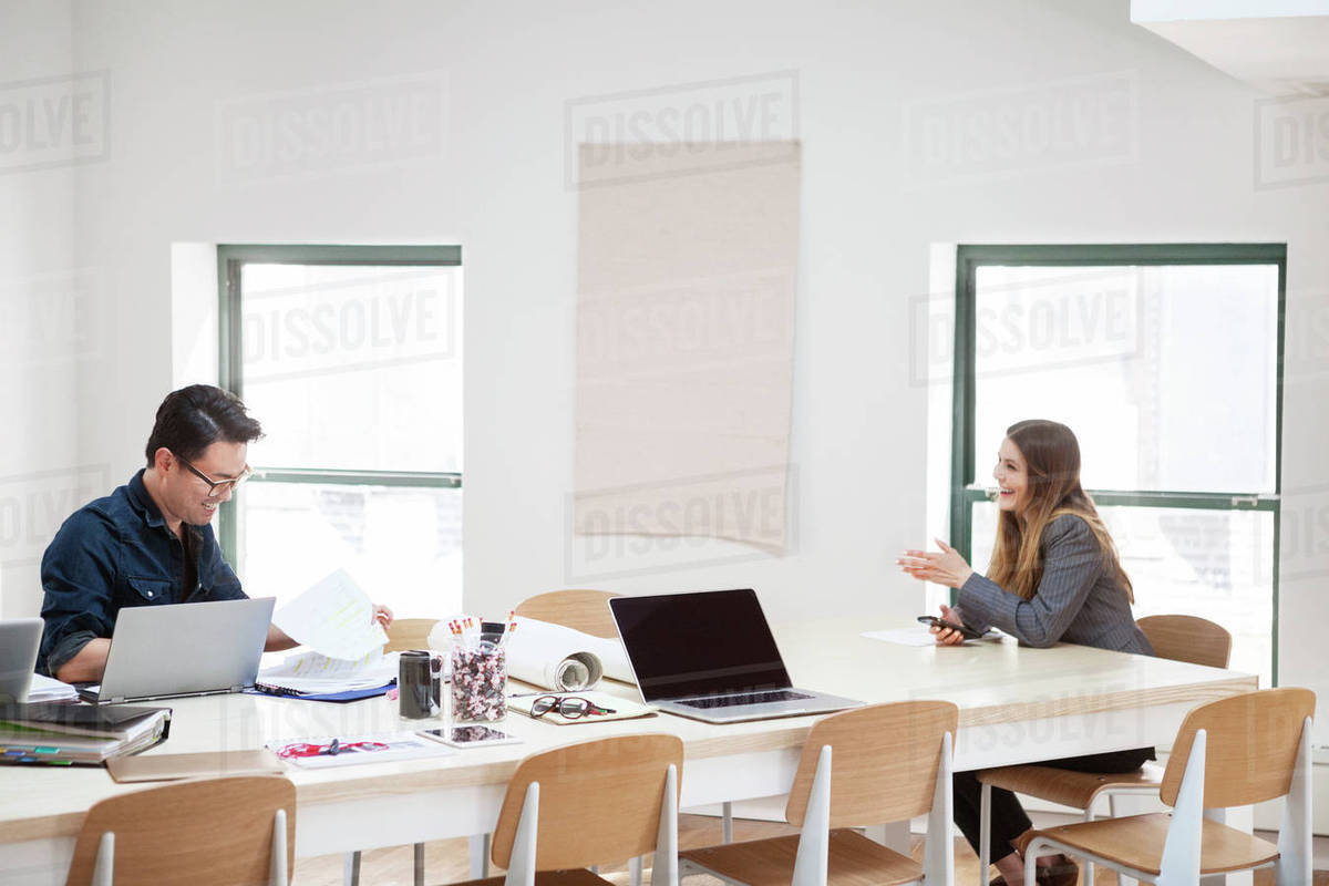 Happy businesswoman discussing with male colleague in creative office Royalty-free stock photo