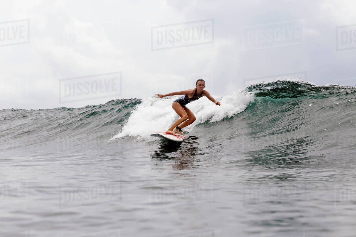 Woman surfboarding on wave in sea against cloudy sky Royalty-free stock photo