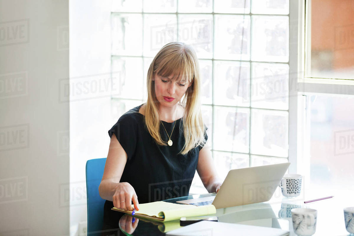 Businesswoman using laptop on table in creative office