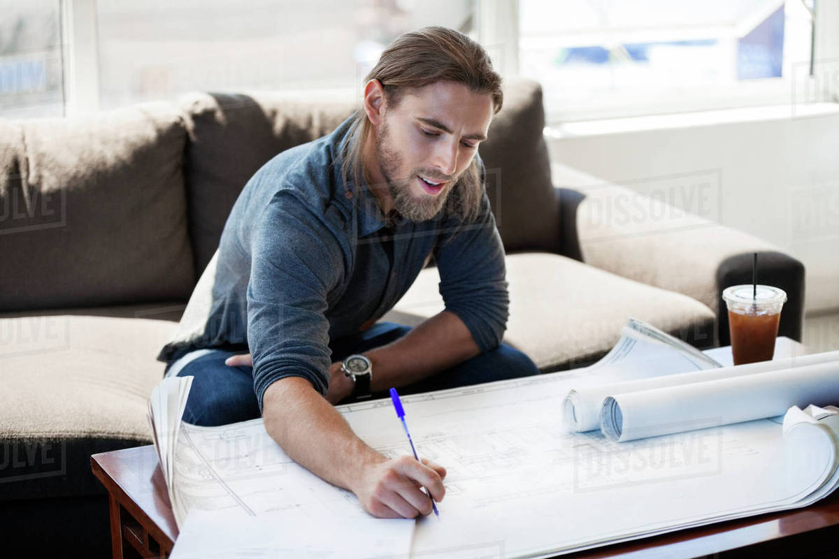 Businessman writing on blueprint in creative office Royalty-free stock photo