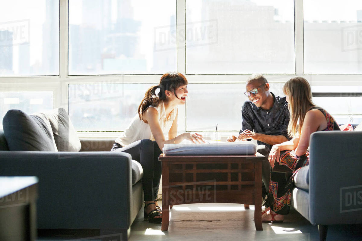 Happy business people discussing about blueprint in creative office Royalty-free stock photo