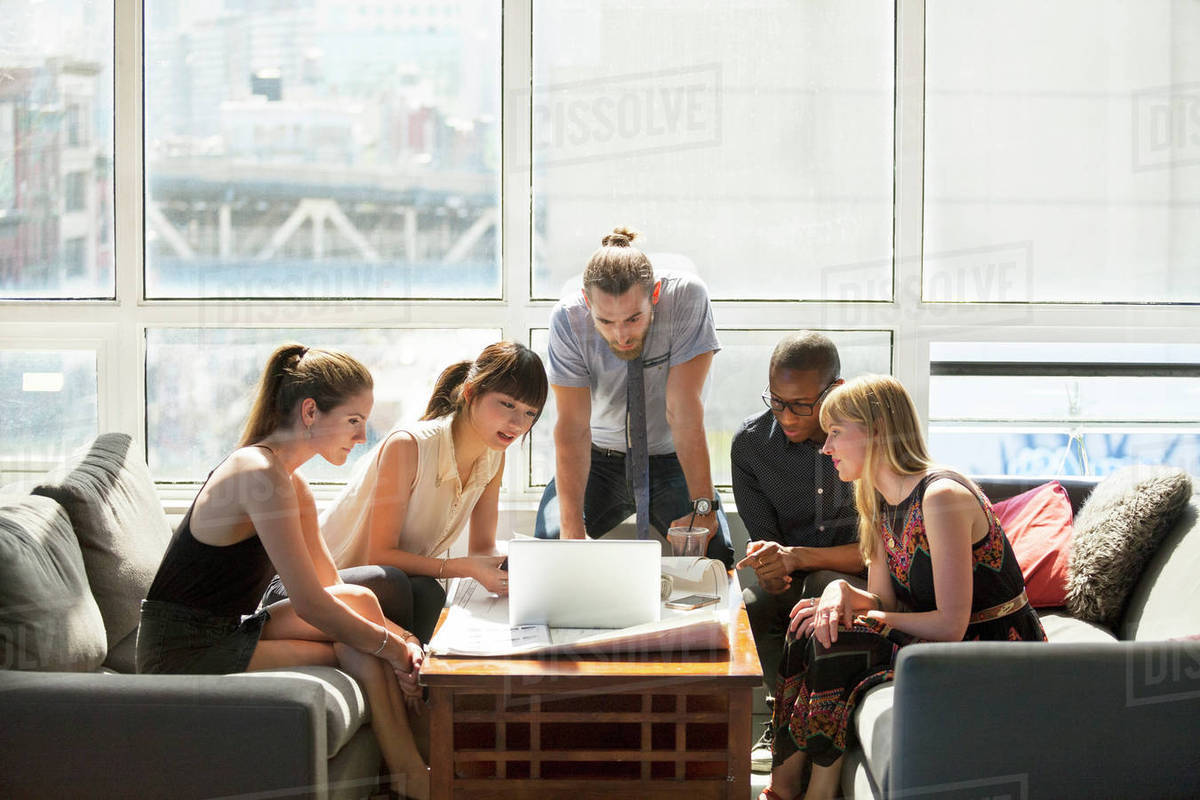 Business people looking at laptop on table in creative office Royalty-free stock photo