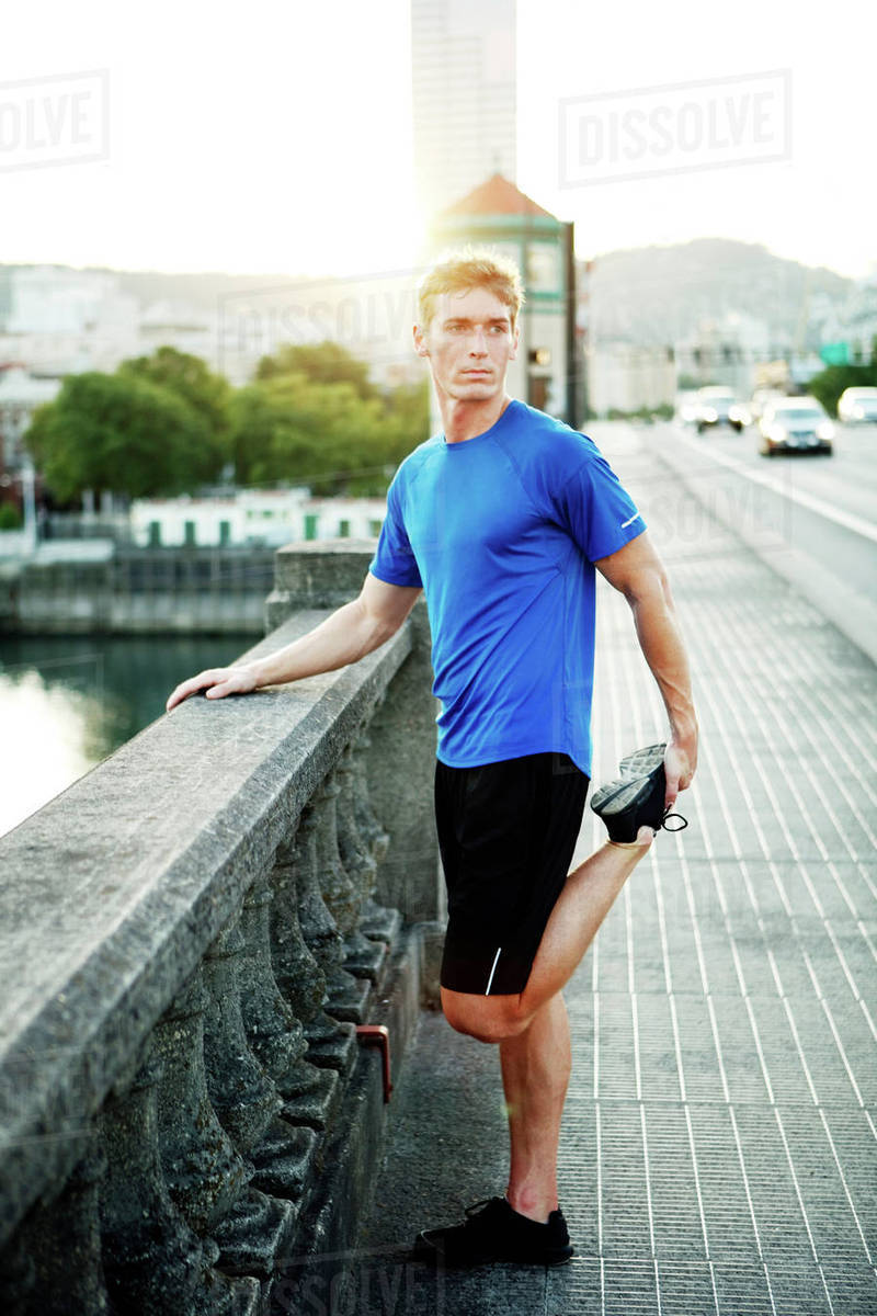 Sporty man exercising on footpath in city Royalty-free stock photo