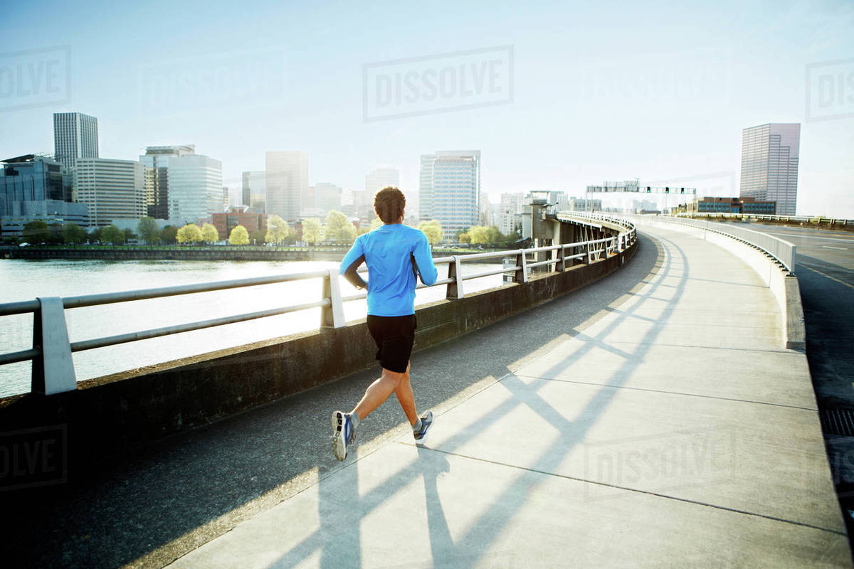 Rear view of male athlete running on bridge against clear sky Royalty-free stock photo