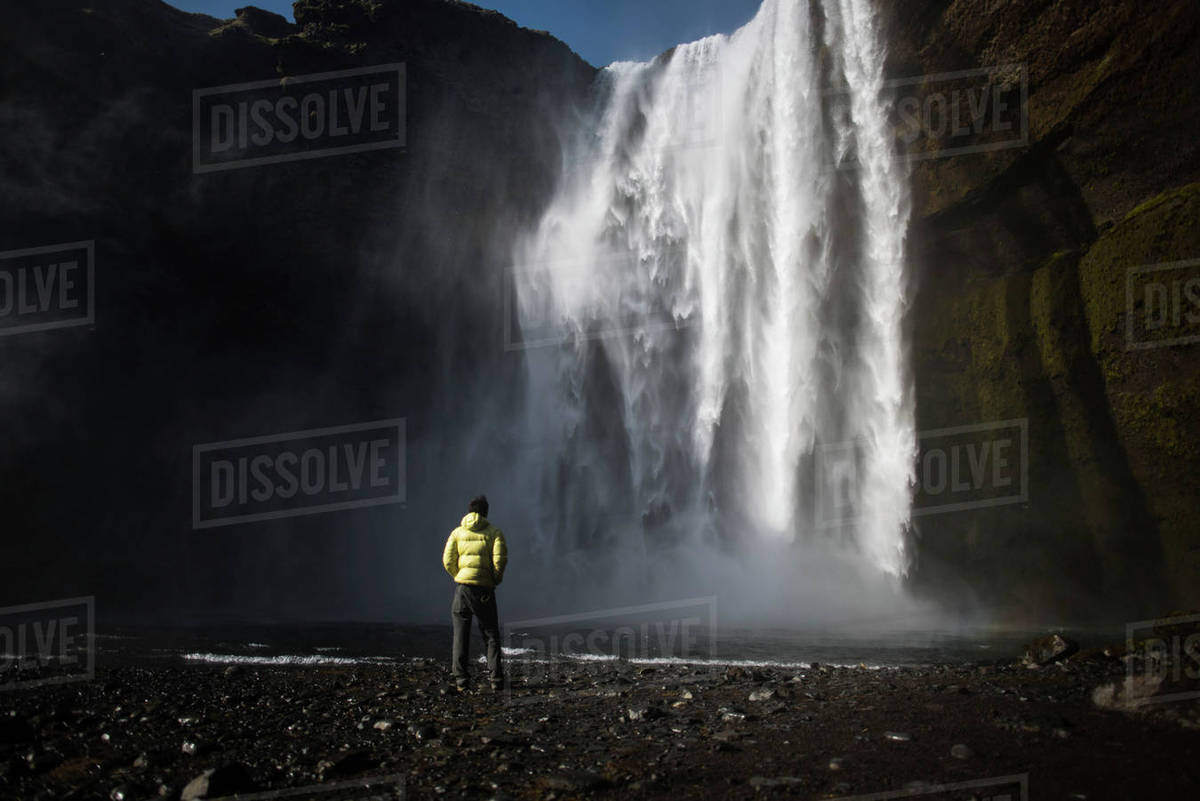 Rear view of man looking at waterfall Royalty-free stock photo