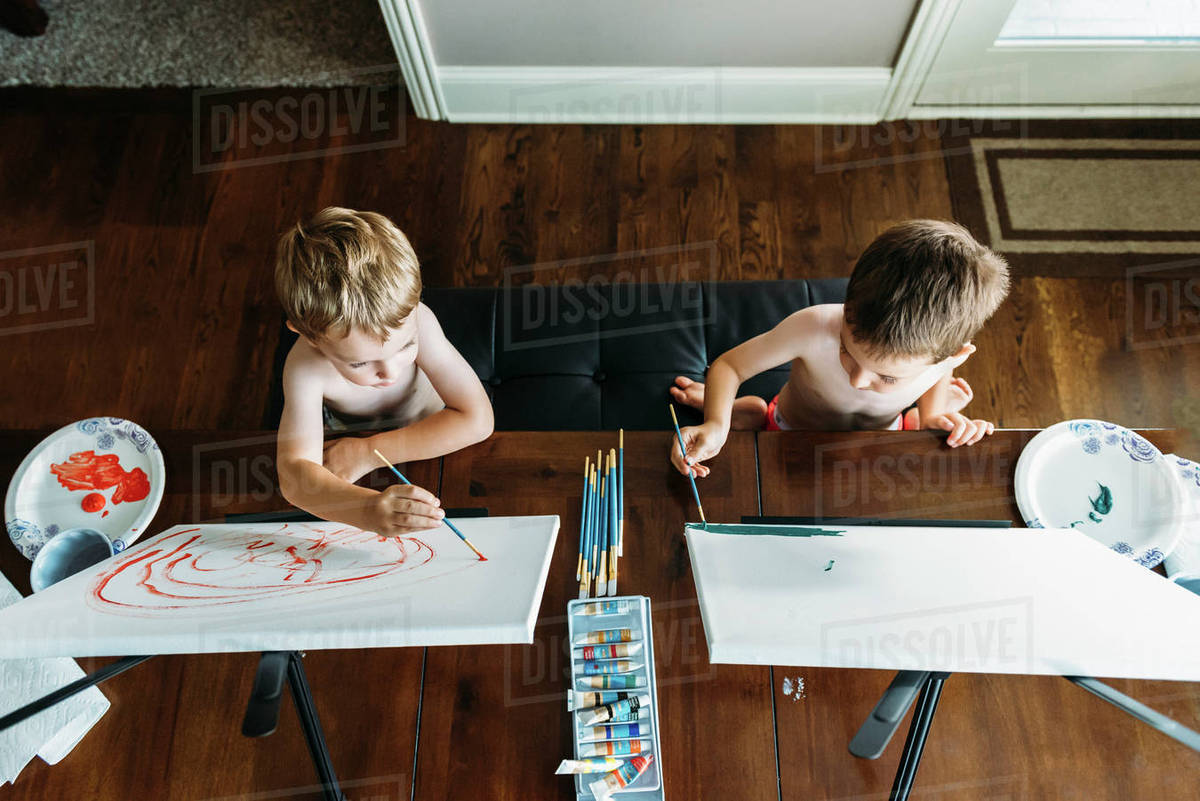 Overhead view of shirtless boys painting on canvas at home Royalty-free stock photo