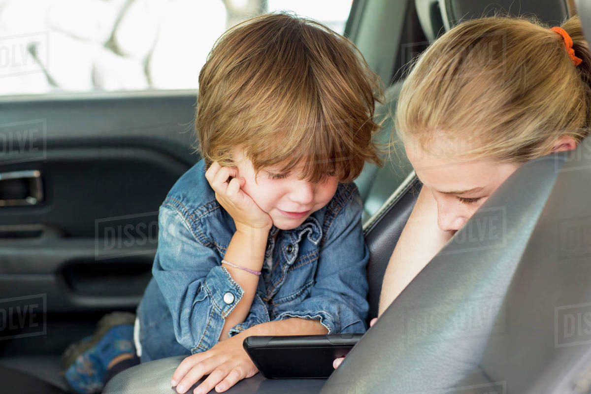 Siblings using mobile phone in car Royalty-free stock photo