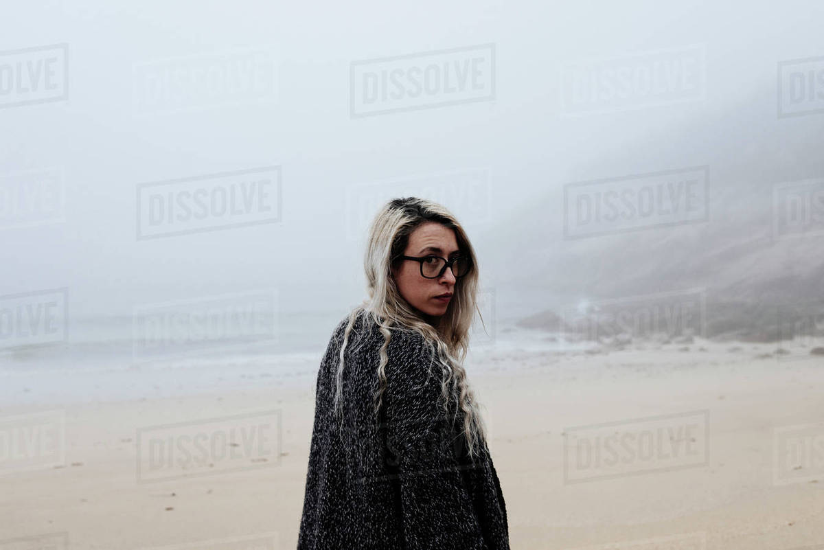 Portrait of woman standing at beach during foggy weather Royalty-free stock photo