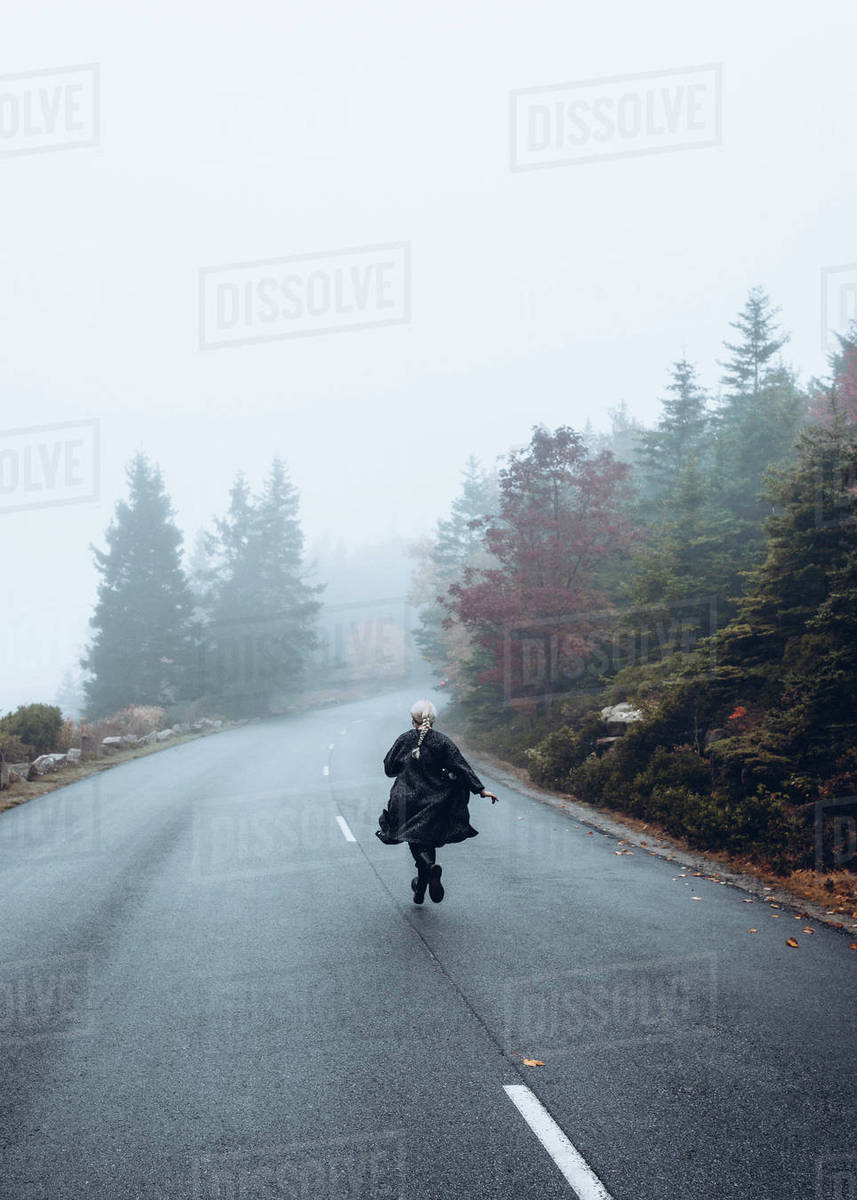 Rear view of woman running on road against sky during foggy weather Royalty-free stock photo