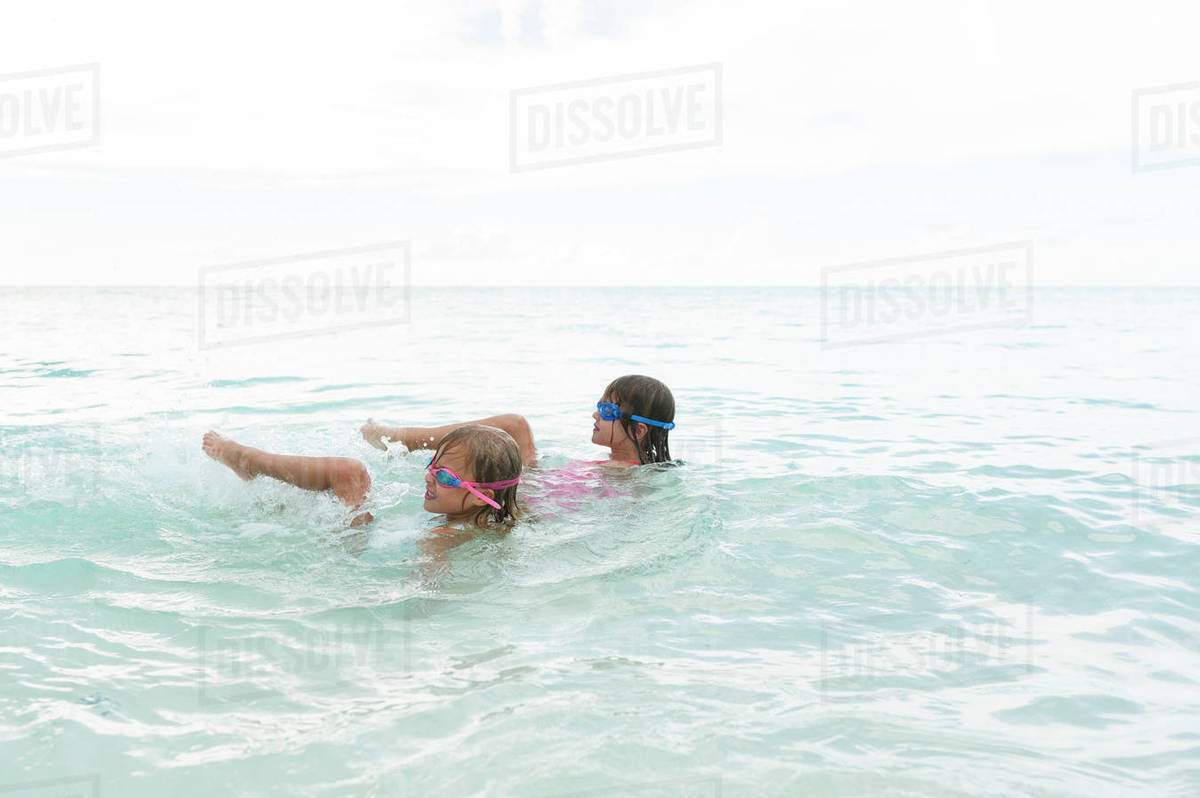 Happy sisters swimming in sea against sky Royalty-free stock photo