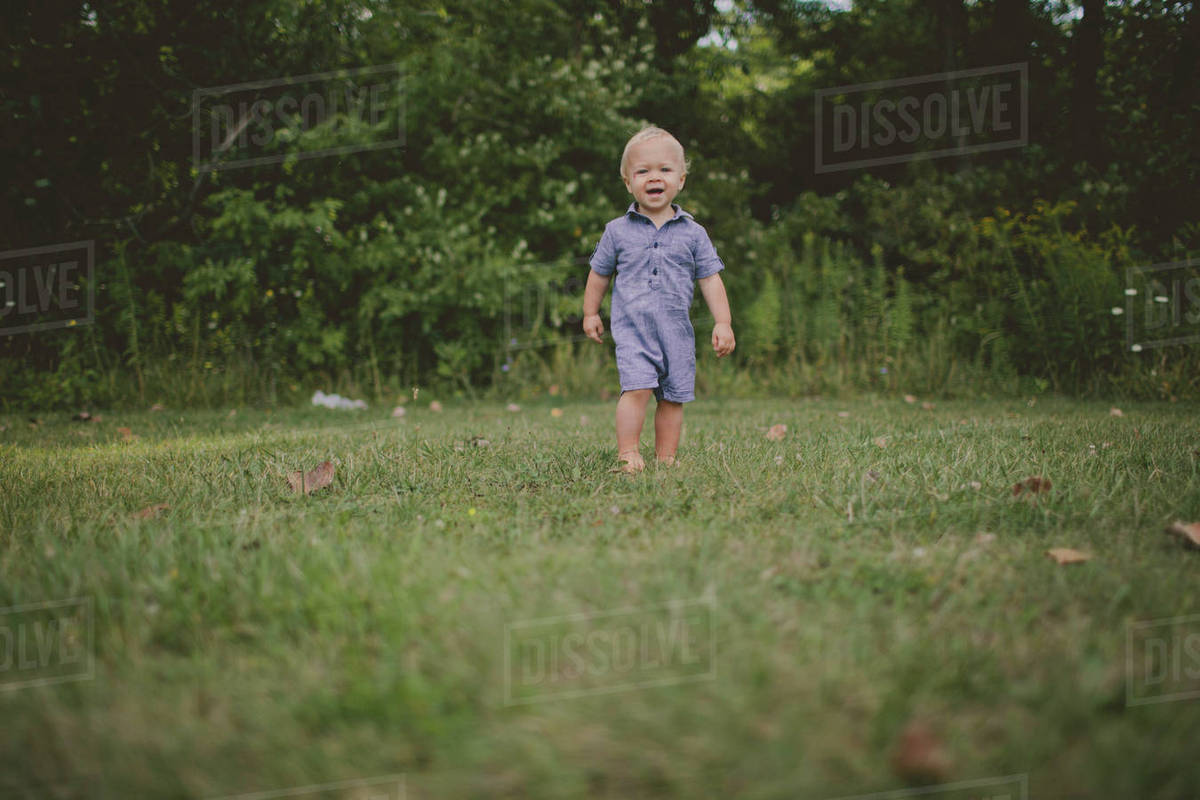 Baby boy walking on grassy field in park Royalty-free stock photo