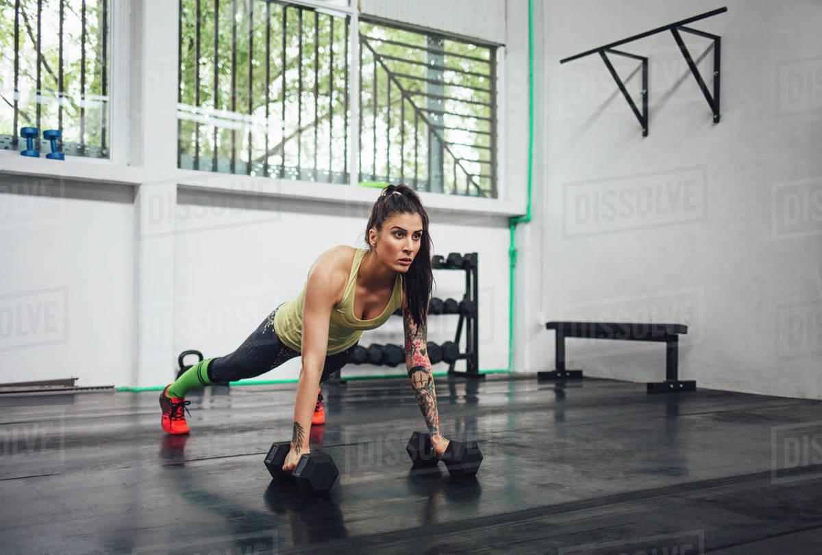 Athlete doing dumbbell push-ups in gym Royalty-free stock photo