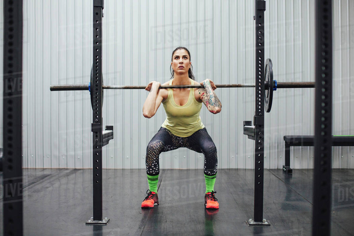 Confident woman lifting barbell in gym Royalty-free stock photo