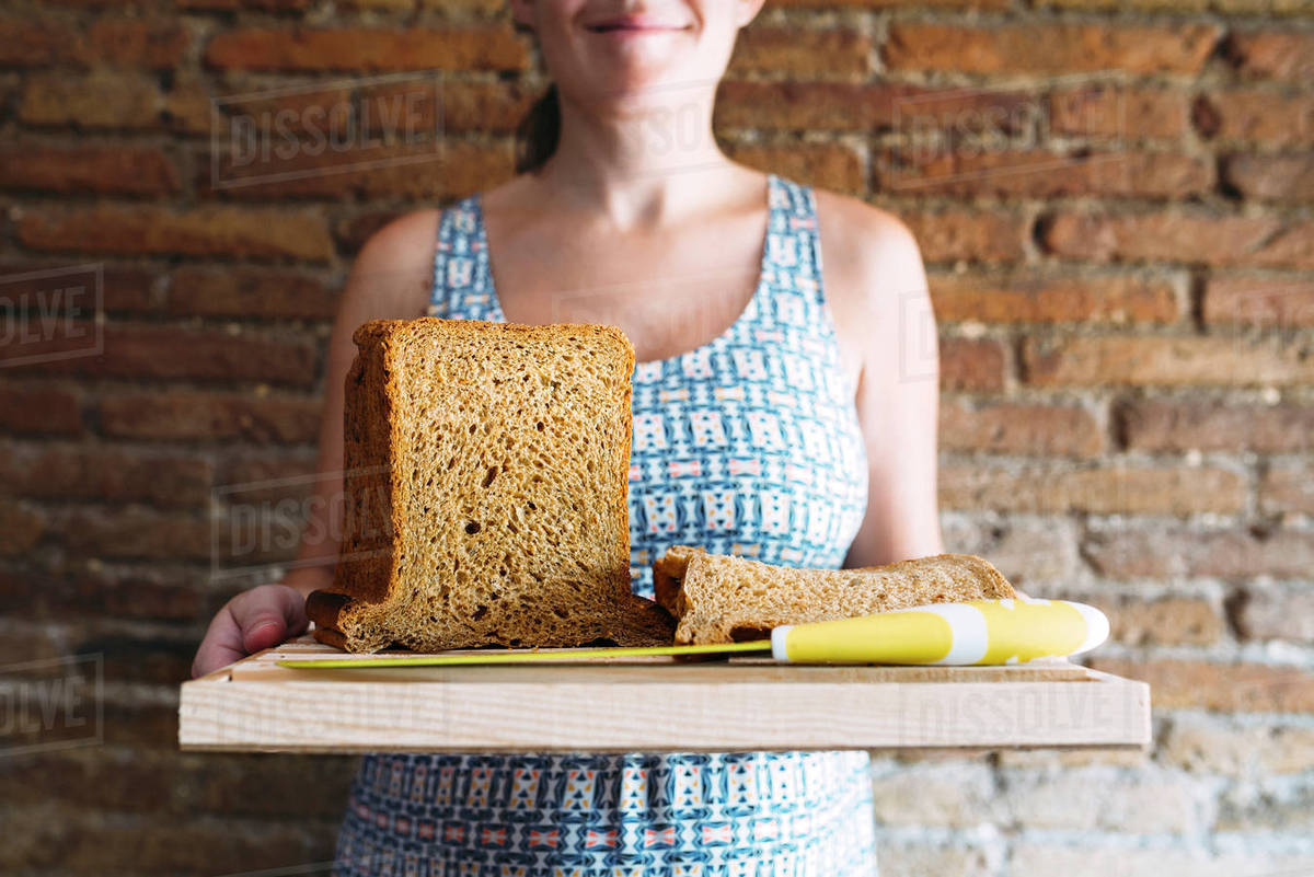 Midsection of woman holding cutting board with bread and kitchen knife against brick wall Royalty-free stock photo