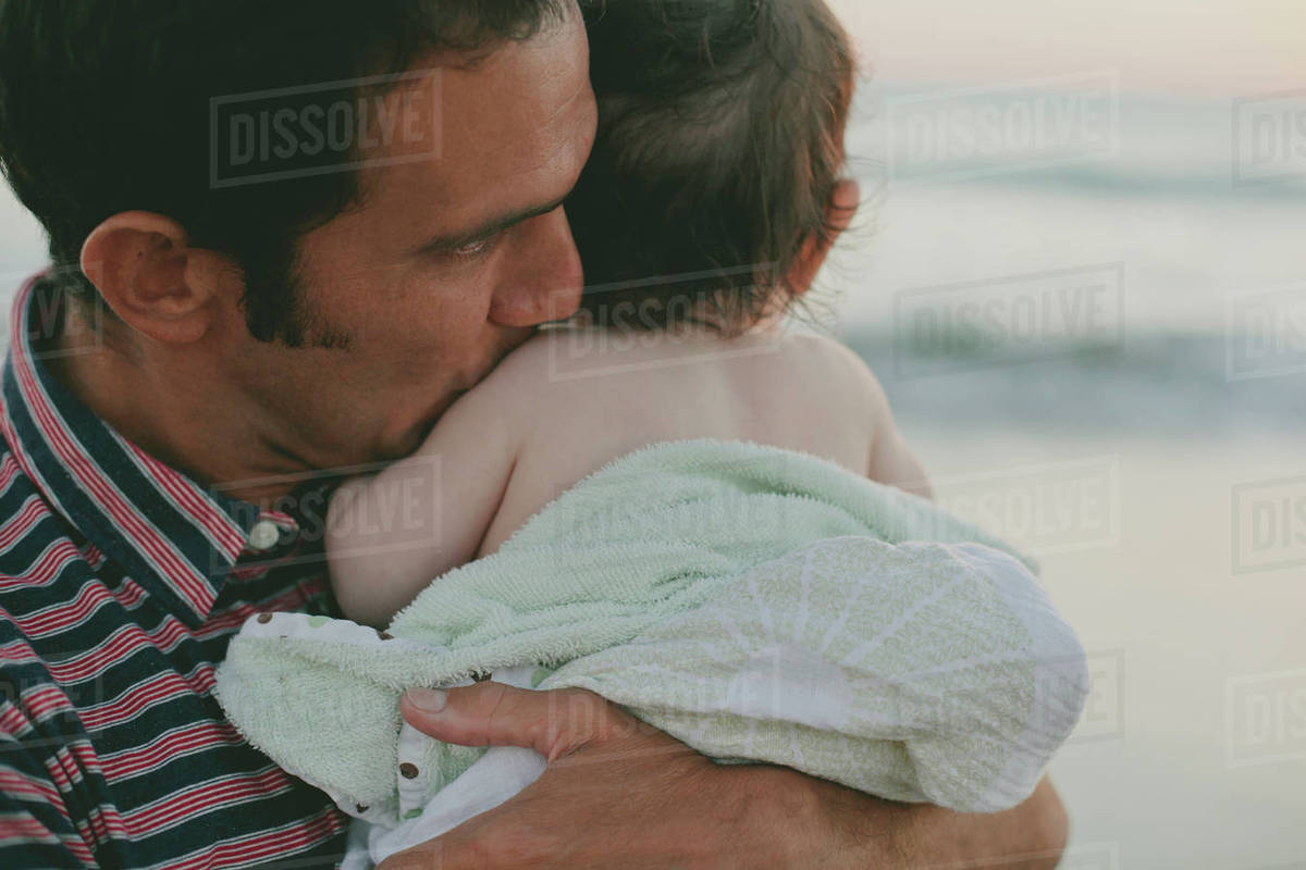 Father kissing son while standing at beach Royalty-free stock photo